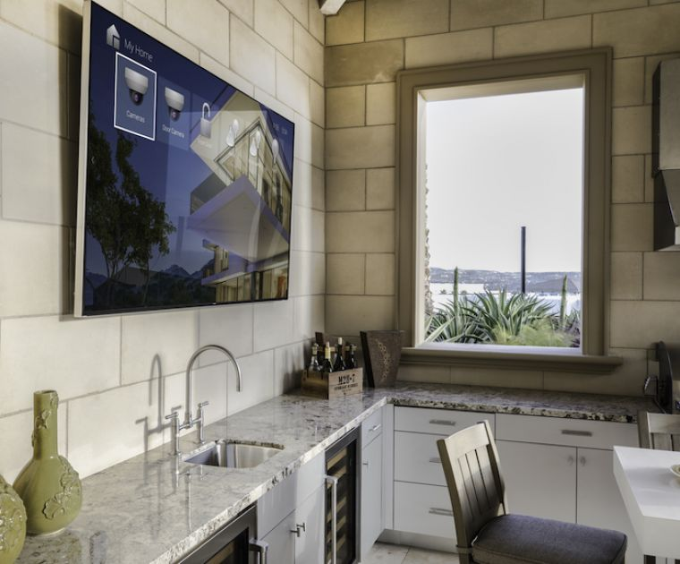 Modern kitchen with large screen TV on wall