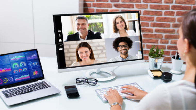 Woman in white top attending a video conference from home with 2 screens