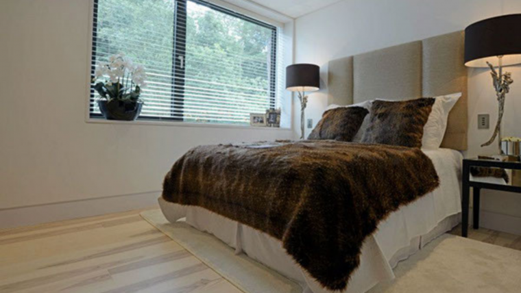 Sandbanks Road - luxury bedroom with Super King sized bed white sheets and rich brown bedspread with a light oak wooden floor.